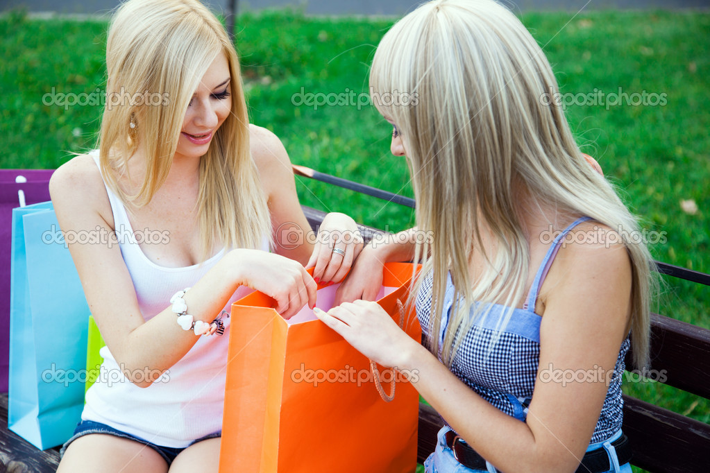 Two beautiful girl friends with shopping bags in a park — Stock Photo #12332973
