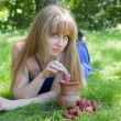 The woman in a grass and a strawberry with milk — Stock Photo
