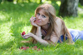 The woman with a strawberry on a grass — Stock Photo