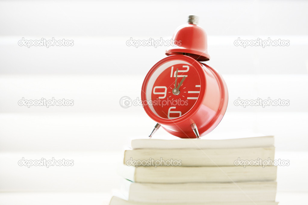 A red traditional alarm clock stand on books — Stock Photo #10764018
