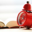 Open book with red alarm clock — Stock Photo