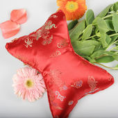 Embroidered pillow and chrysanthemum — Stock Photo