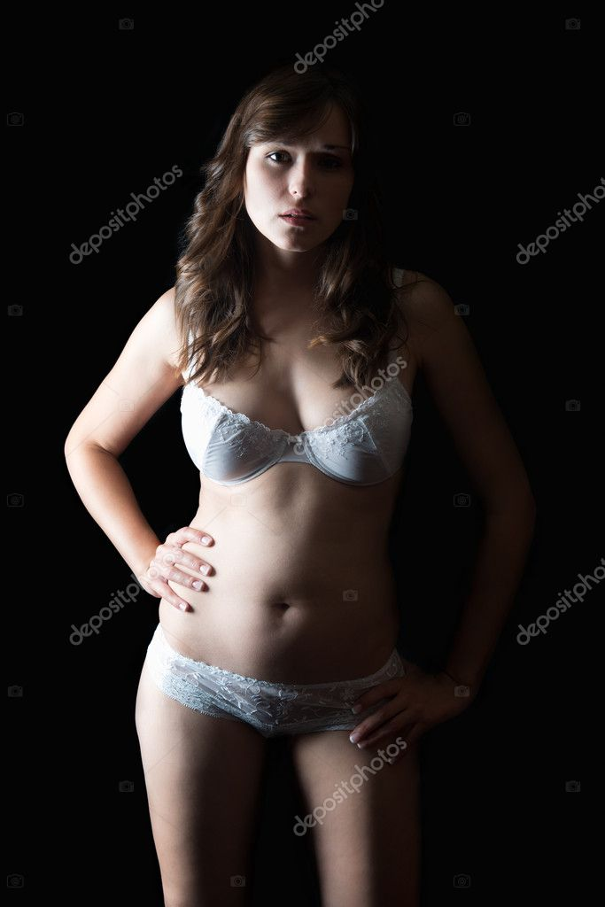 Portrait of a young woman in beautiful white underwear in front of black background  Stock Photo #12128524