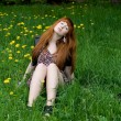 Royalty-Free Stock Photo: Girl sitting on a field of dandelions