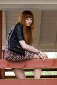 Girl sitting on a veranda — Stock Photo