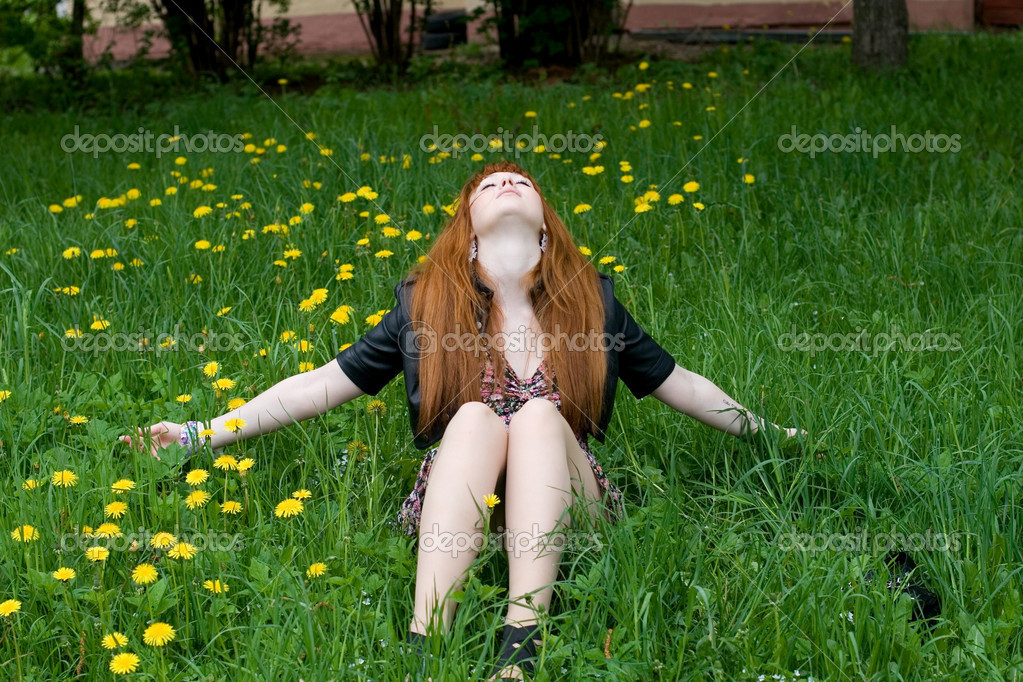 Girl sitting on a field of dandelions  Stock Photo #10800732