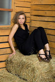 Girl sitting on hay — Stock Photo