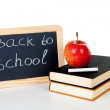 Blackboard slate and stack of books with apple on top — Stock Photo #11334851