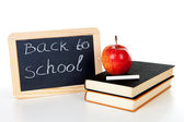 Blackboard slate and stack of books with apple on top — Stock Photo