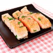 Plate with fresh salmon on checkered napkin — Stock Photo