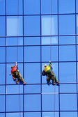 Group of washers wash the glass facade — Stock Photo