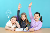 Three happy girls doing their school work — Photo
