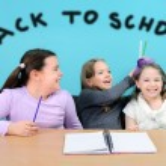 Happy school girls making jokes in classroom — Stock Photo