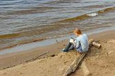 Een meisje, zittend op een logboek in de buurt van de rivier. — Stockfoto