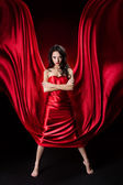 Mysterious woman in red waving silk dress over black background — Stock Photo