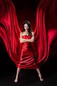 Vestido de mulher misteriosa em acenos de seda vermelha sobre fundo preto — Fotografia Stock