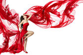 Beautiful woman dancing in red dress flying on a wind flow over — Photo