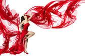 Linda mulher dançando vestida de vermelho em um fluxo de vento sobrevoando — Foto Stock