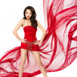Stock Photo: Beautiful womstanding in red flying dress. Hands on hips. Chi