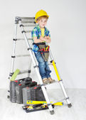 Little boy handyman with helmet and tool belt on stepladder — Stock Photo