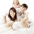 Happy family: parents playing with two kids in bed. Looking at c — Stock Photo #11267800