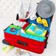 Stock Photo: Travel suitcase packed for vacation with personal belongings