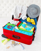 Travel suitcase packed for vacation with personal belongings — Stock Photo