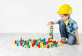 Boy in hard hat playing with blocks: building city — 图库照片
