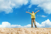 Happy child standing with hands raised up over blue sky — Stock Photo