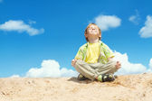 Happy child sitting in lotus position over bllue sky — Stock Photo