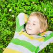 Little child sleeping outdoors on grass, hands behind head. High — Stock Photo
