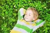 Little child sleeping outdoors on grass, hands behind head. High — Stock Photo