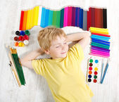 Child dreaming lying next to pencils, brushes and paints. Creat — Stock Photo