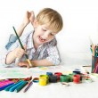 Happy child drawing with brush by multicolor paints — Stock Photo #12178470