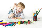 Happy child drawing with brush by multicolor paints — Photo