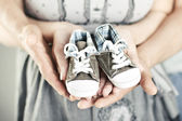 Newborn baby booties in parents hands — Stock Photo