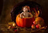 Child in cap inside pumpkin. Basket with autumn harvest — Stock Photo