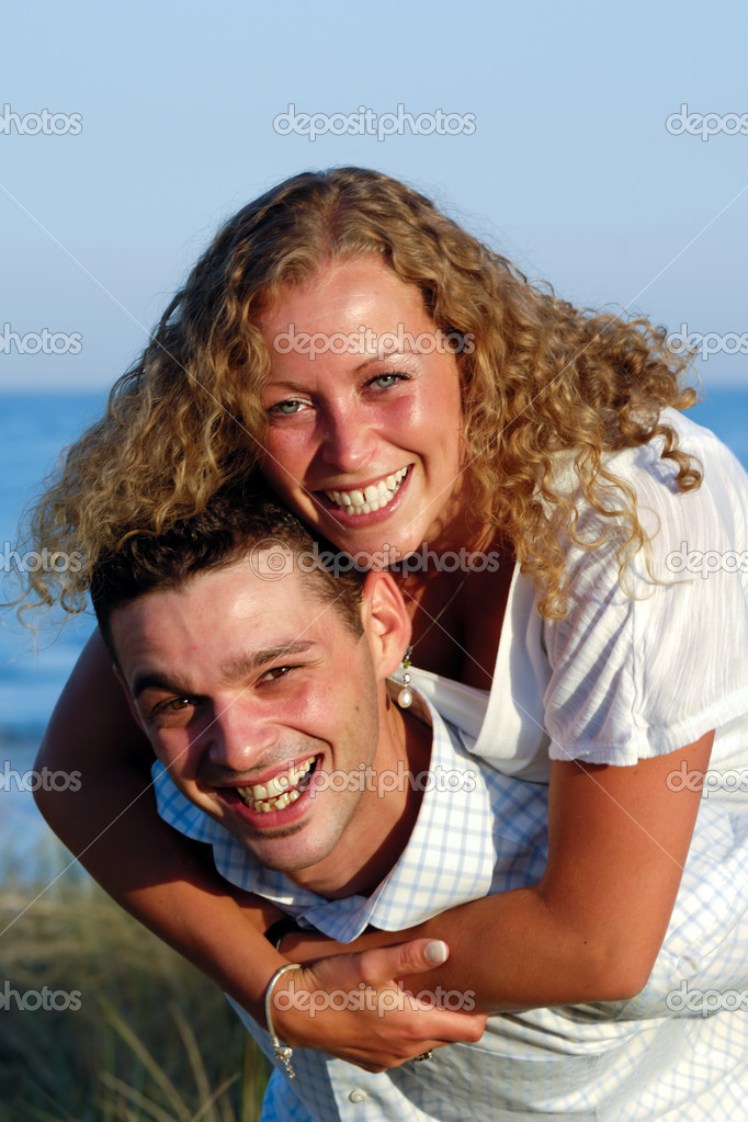 A happy woman and man in love at beach. The young man is carrying his girlfriend on the back of his shoulders. — Stock Photo #11009063
