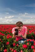Jovem com câmera de foto antiga em campo com tulipas — Fotografia Stock