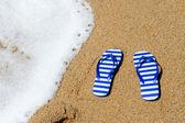Gestreifte flip-flops am strand — Stockfoto