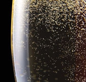 Champagne in wineglass on a black background — Stock Photo