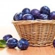 Ripe plums in basket on a wood table — Stock Photo #12044387