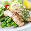 Fried fish on green asparagus with salad - Stock Photo