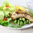 Fried fish on green asparagus with salad — Stock Photo