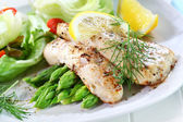 Fried fish on green asparagus with salad — ストック写真