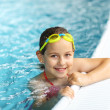 Girl with goggles in swimming pool - Stock Photo