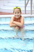 Child relaxing by swimming pool — Stock Photo