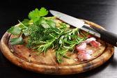 Herbs on wooden platter — Stock Photo