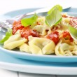 Tortellini with tomato sauce and cheese - Stock Photo
