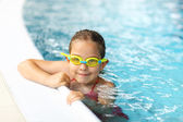 Schoolgirl with goggles in swimming pool — Stok fotoğraf